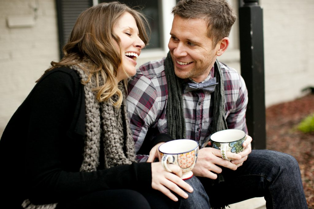 man and woman smiling and laughing holding coffee cups