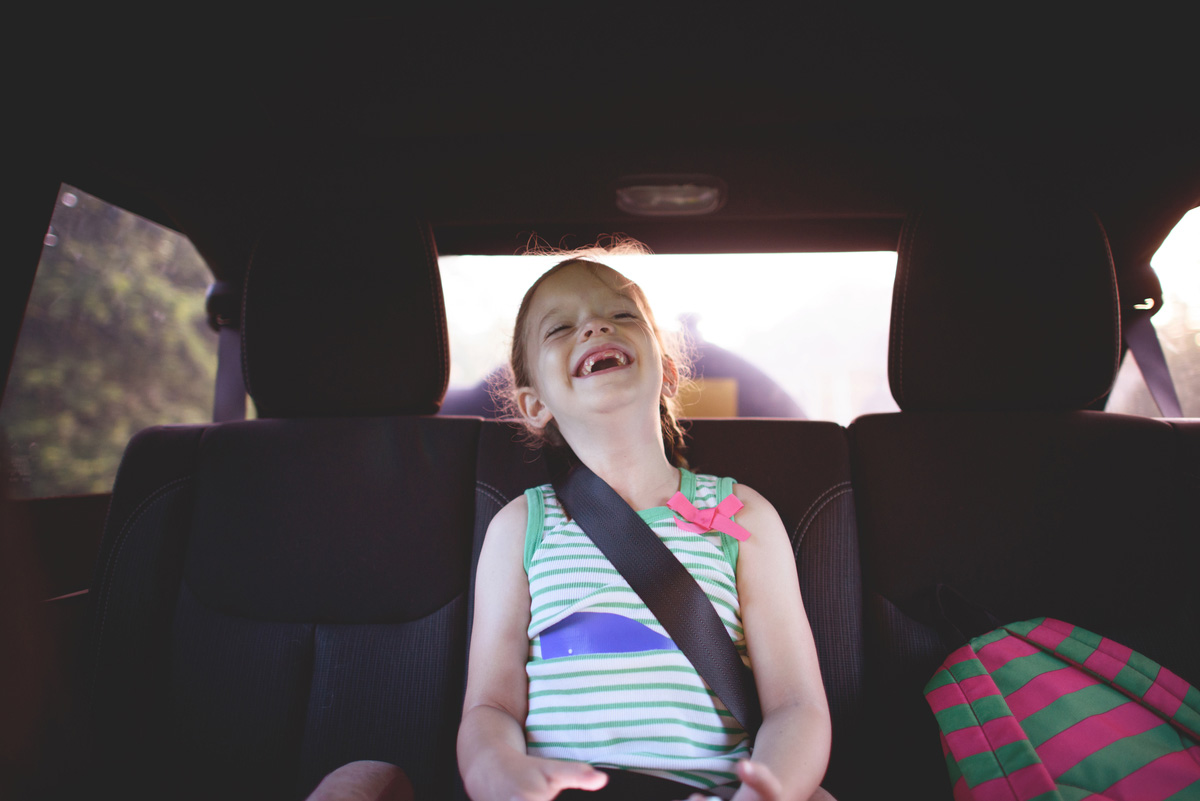 little girl laughing in car