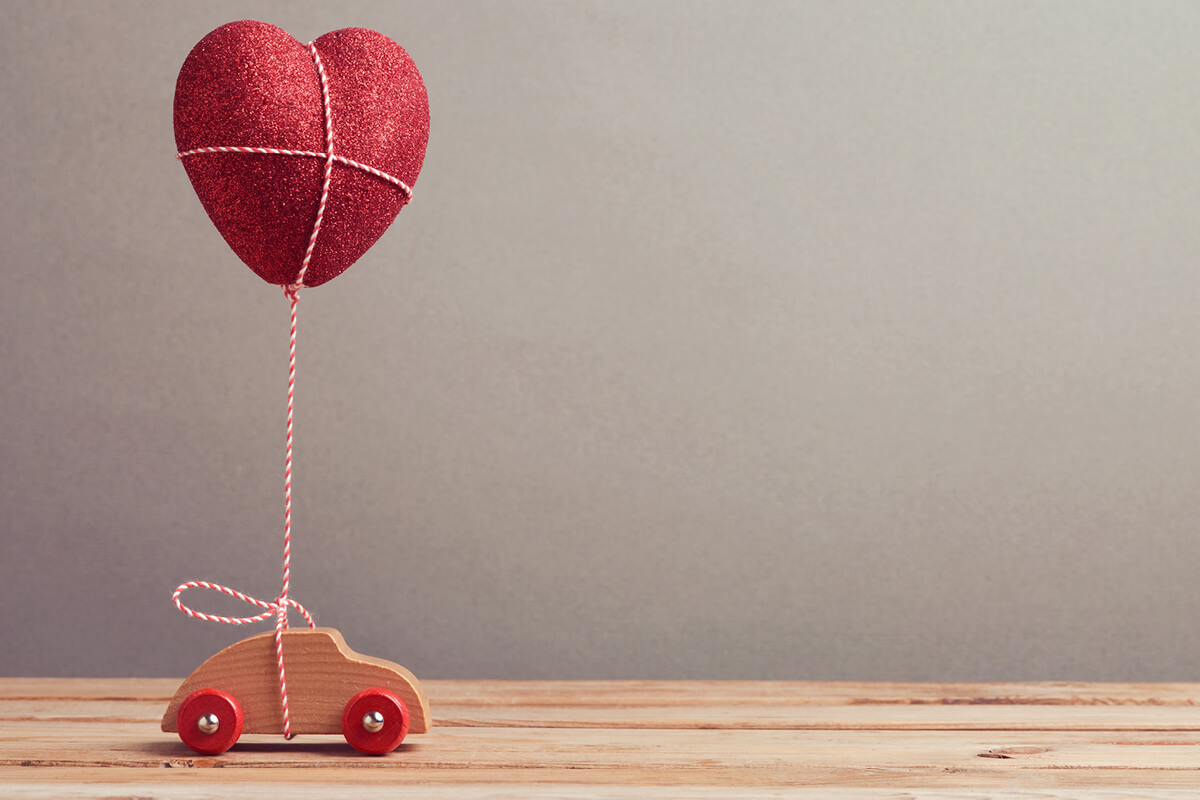 small wooden child's play toy of a car rolling along holding a heart balloon