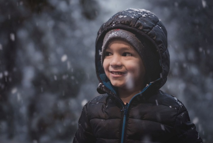 kid outside in coat under falling snow