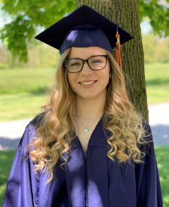 Molli standing in front of a tree smiling. She is wearing her cap and gown for graduation.