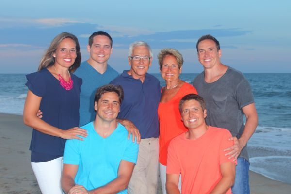 The Leman family photo. They are smiling on the beach. There is a young women on the left and then two young men, an older couple, the mom and dad and then two other young men.