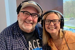 randy and monica middle aged couple with glasses they are smiling and wearing radio headphones