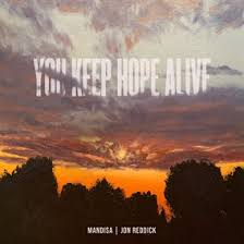 You Keep Hope Alive All caps in front of a strong looking cloud that is over a sunset or sunrise with dark trees that are in the shadows at the bottom of the photo Mandisa and Jon Reddick's names are in a small font at the bottom of this image