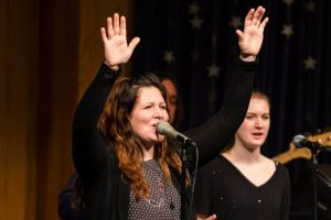 Kati Pessin singing at church in front of microphone with her hands raised