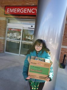 Christina standing in front of an emergency department holding a box of Girl Scout Cookies