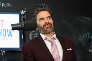 brant hansen sitting next to a radio microphone
