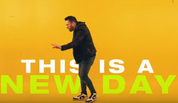 "Danny Gokey dancing in front of ""THIS IS A NEW DAY"""