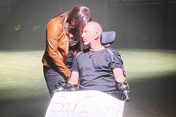 """Gary in wheel chair, kelly is hugging him with a """"Say I Won't"""" sign in his lap"""