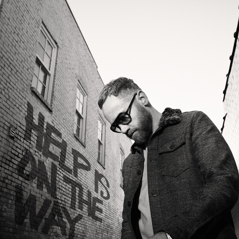 TobyMac with sunglasses Help is on the way painted on the building he is standing next to