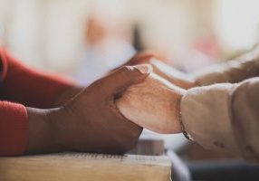black hands holding white hands praying over a Bible together