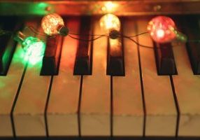 piano keys with Christmas lights laid on top