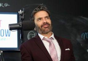 brant hansen sitting next to a radio microphone