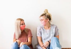 two young women wearing colorful face masks sitting down looking happy