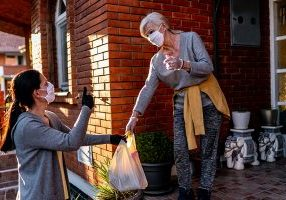 Women exchanging groceries on porch wearing masks
